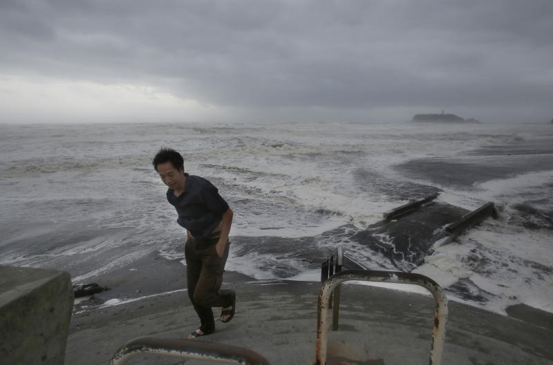 A man walks back from Enoshima beach as a typhoon approaches nearby in Fujisawa, near Tokyo, Monday, Sept. 16, 2013. Powerful typhoon Man-yi was bearing down on Japan and went past Tokyo on Monday, leaving one dead and dumping torrential rains, damaging homes and flooding parts of the country's popular tourist destination of Kyoto, where hundreds of thousands of people were ordered to evacuate to shelters. (AP Photo/Shizuo Kambayashi)