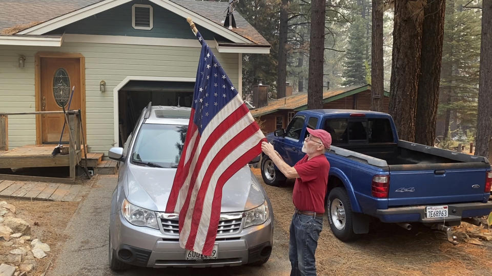 FILE - In this Tuesday, Aug. 31, 2021, file photo, Bill Roberts rolls up an American flag in front of his house in South Lake Tahoe, Calif., a day after the city was ordered to evacuate because of the approaching Caldor Fire. State fire officials say evacuation orders for the area were reduced to warnings as of 3 p.m. on Sunday, Sept. 5. Some 22,000 people had been forced to flee the popular resort and nearby areas last week as the Caldor Fire roared toward it. (AP Photo/Terry Chea, File)