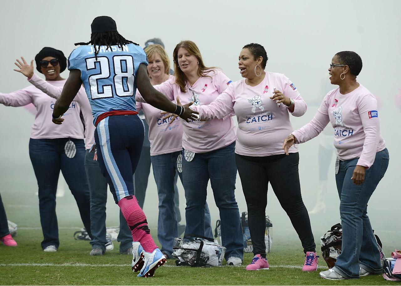Tennessee Titans running back Chris Johnson (28) slaps hands with breast cancer survivors as he is introduced before an NFL football game between the Titans and the Kansas City Chiefs on Sunday, Oct. 6, 2013, in Nashville, Tenn. (AP Photo/Mark Zaleski)