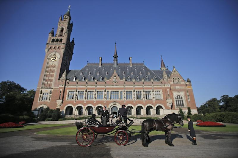 FILE - In this Aug. 28, 2013 file photo, a horse-drawn carriage stands in front of the Peace Palace, seat of the International Court of Justice (ICJ) in The Hague, Netherlands, Wednesday, Aug. 28, 2013. The tiny Pacific nation of the Marshall Islands that was used for dozens of U.S. nuclear tests after World War II is taking on the United States and the world's eight other nuclear-armed nations with an unprecedented lawsuit demanding that they meet their obligations toward disarmament and accusing them of 'flagrant violations' of international law. The suit was filed on Thursday, April 24, 2014 at the ICJ. (AP Photo/Peter Dejong, File)