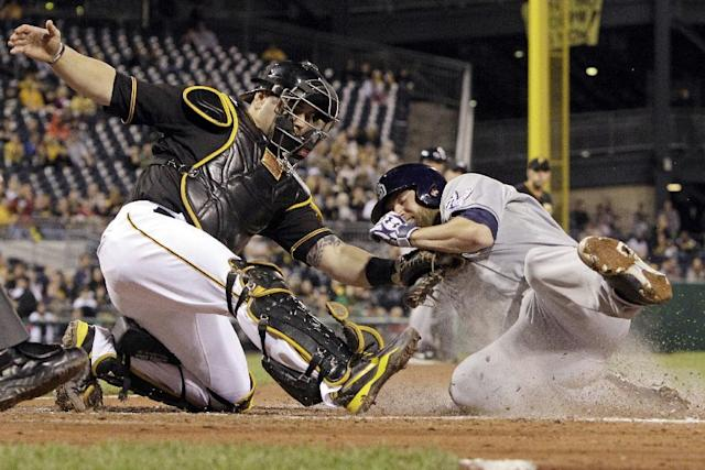 San Diego Padres' Andrew Cashner, right, scores ahead of the tag by Pittsburgh Pirates catcher Russell Martin,left, during the seventh inning of a baseball game against the Pittsburgh Pirates in Pittsburgh Monday, Sept. 16, 2013. Cashner scored from second on a single by Padres' Jedd Gyorko of Pittsburgh Pirates starting pitcher A.J. Burnett. (AP Photo/Gene J. Puskar)