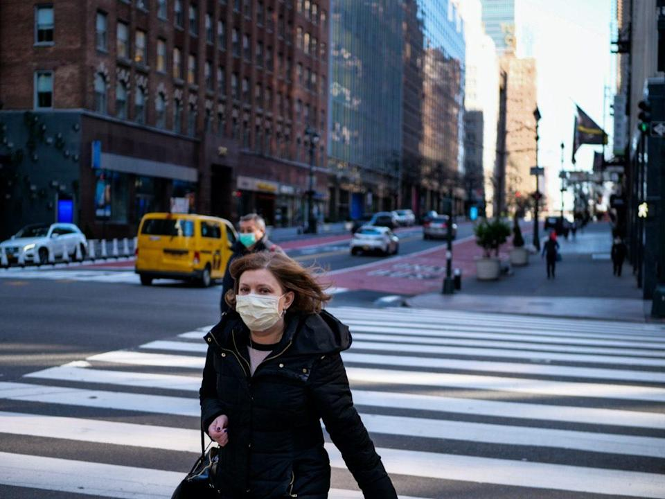 woman with mask walking in nearly empty new york street