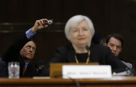 A member of the audience takes a picture as Janet Yellen, President Barack Obama's nominee to lead the U.S. Federal Reserve, prepares to testify at her U.S. Senate Banking Committee confirmation hearing in Washington, November 14, 2013. REUTERS/Jason Reed