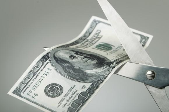 Scissors cutting a $100 bill in half.