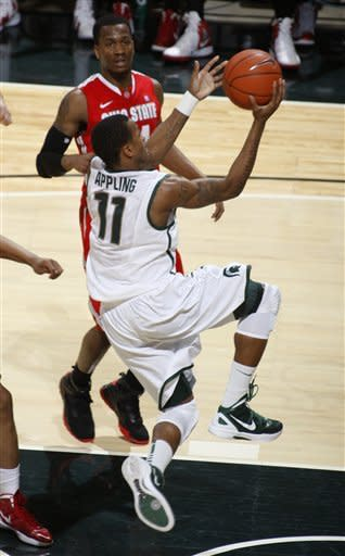 Michigan State's Keith Appling (11) puts up a layup in front of Ohio State's William Buford during the first half of an NCAA college basketball game, Sunday, March 4, 2012, in East Lansing, Mich. (AP Photo/Al Goldis)