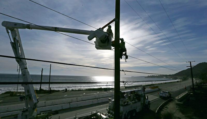 In this Nov. 13 photo, Southern California Edison crews work to replace burned power poles and lines destroyed by the Woolsey Fire on Pacific Coast Highway in Malibu.