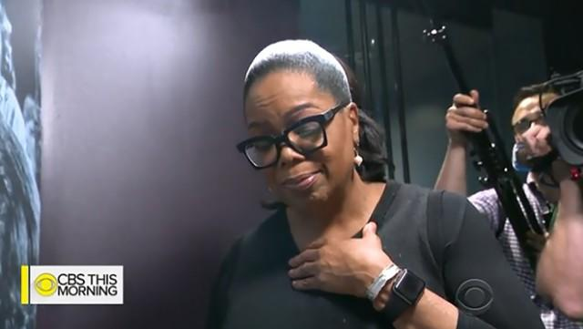Oprah Winfrey cries as she tours the Smithsonian exhibit dedicated to her.