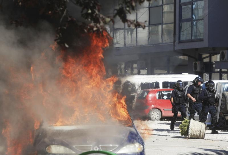 Police walk past a burning car set on fire by Kosovo Albanians during a protest in the ethnically divided town of Mitrovica