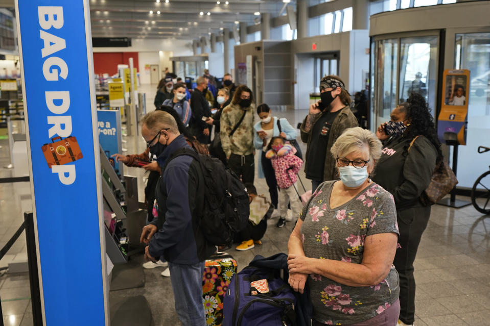 Vickie Lechuk, right, waits in line to check baggage at Cleveland Hopkins International Airport, Wednesday, Nov. 25, 2020, in Cleveland. Lecuk is traveling to Tampa, Florida. (AP Photo/Tony Dejak)