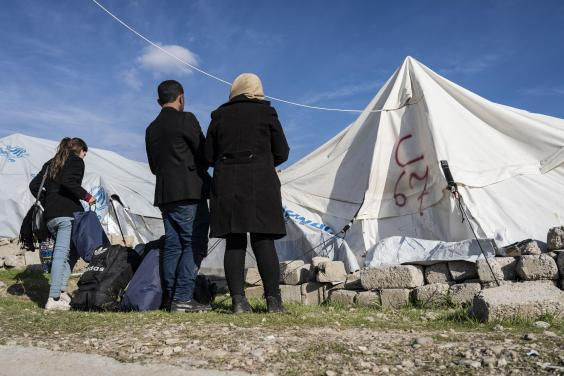 A couple who recently fled conscription in northern Syria stand outside the tent assigned to them (Bel Trew)
