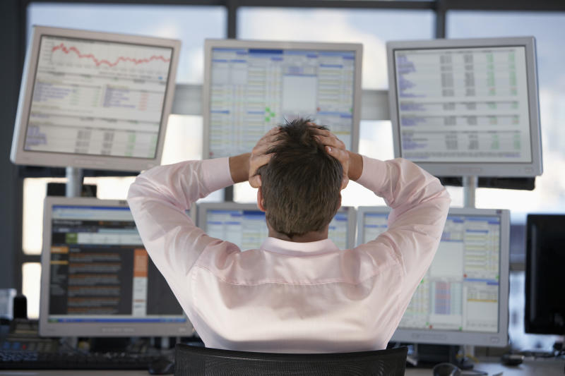 A visibly frustrated stock trader grasping his head as he looks at six different monitors showing stock charts and numbers