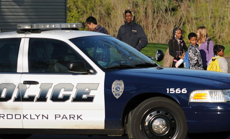 People watch police investigate the scene where three people were shot and killed at an in-home day care in Brooklyn Park,  Minn., on Monday, April 9, 2012. No arrests were immediately made. (AP Photo/The Star Tribune, Richard Sennott)  MANDATORY CREDIT; ST. PAUL PIONEER PRESS OUT; MAGS OUT; TWIN CITIES TV OUT