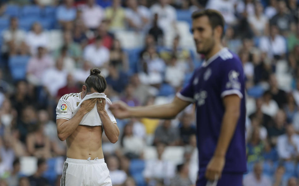 Real Madrid's Gareth Bale, left, gestures during the Spanish La Liga soccer match between Real Madrid and Valladolid at the Santiago Bernabeu stadium in Madrid, Spain, Saturday, Aug. 24, 2019. (AP Photo/Paul White)