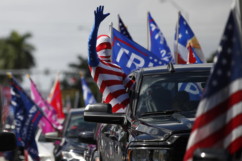 A man wearing a flag-themed body stocking waves from a car as hundreds of vehicles gather at Tropical Park ahead of a car caravan in support of President Donald Trump, in Miami, Sunday, Nov. 1, 2020. (AP Photo/Rebecca Blackwell)