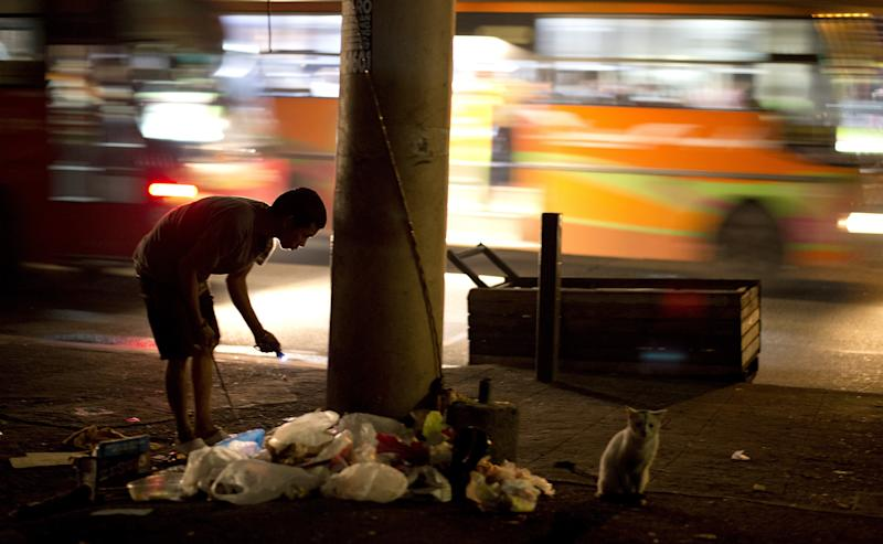 A scavenger goes through rubbish on street in Manila, the Philippines on December 24, 2014 looking for plastic bottles that he can sell to junkshops (AFP Photo/Noel Celis)