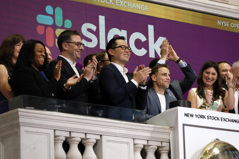 Slack CEO Stewart Butterfield, second from right, is applauded as he rings the New York Stock Exchange opening bell, before his company's IPO, Thursday, June 20, 2019. NYSE President Stacey Cunningham is at right. (AP Photo/Richard Drew)