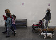 A woman takes her dogs for a stroll in Santiago, Chile, Friday, May 28, 2021, amid the COVID-19 pandemic. (AP Photo/Esteban Felix)