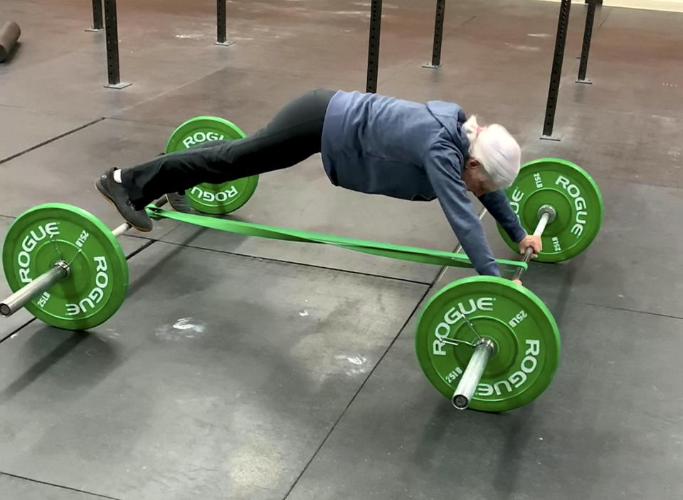 The 73-year-old easily pulls off a plank on top of the weights. (SWNS)
