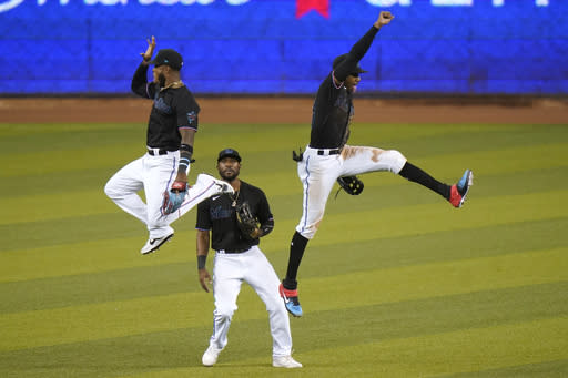 Miami Marlins' Monte Harrison, left, Starling Marte, center, and Lewis Brinson celebrate after the team's baseball game against the Washington Nationals, Saturday, Sept. 19, 2020, in Miami. The Marlins won 7-3. (AP Photo/Lynne Sladky)