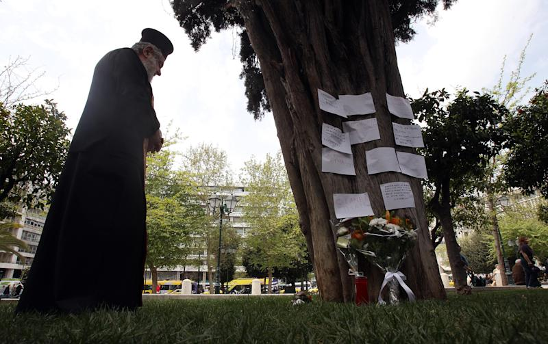 A Greek Orthodox priest holds a memorial service, at the site where an elderly man fatally shot himself at Athens' main Syntagma square, on Wednesday, April 4, 2012. The Greek pensioner picked the busiest public area in Athens to shoot himself dead on Wednesday, leaving a note which police said linked his suicide with the country's acute financial woes. (AP Photo/Thanassis Stavrakis)