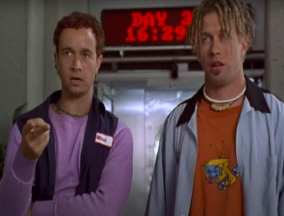 """Bud and Stubs stand in front of a sign that says """"day 3"""" in Bio-Dome"""