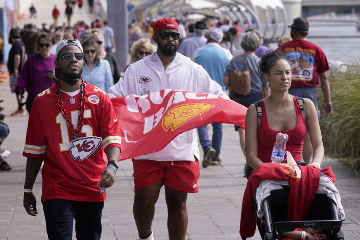 People wear masks as they walk down a sidewalk near Super Bowl 55 activities Friday, Feb. 5, 2021, in Tampa, Fla. The city is hosting Sunday's Super Bowl football game between the Tampa Bay Buccaneers and the Kansas City Chiefs. (AP Photo/Charlie Riedel)
