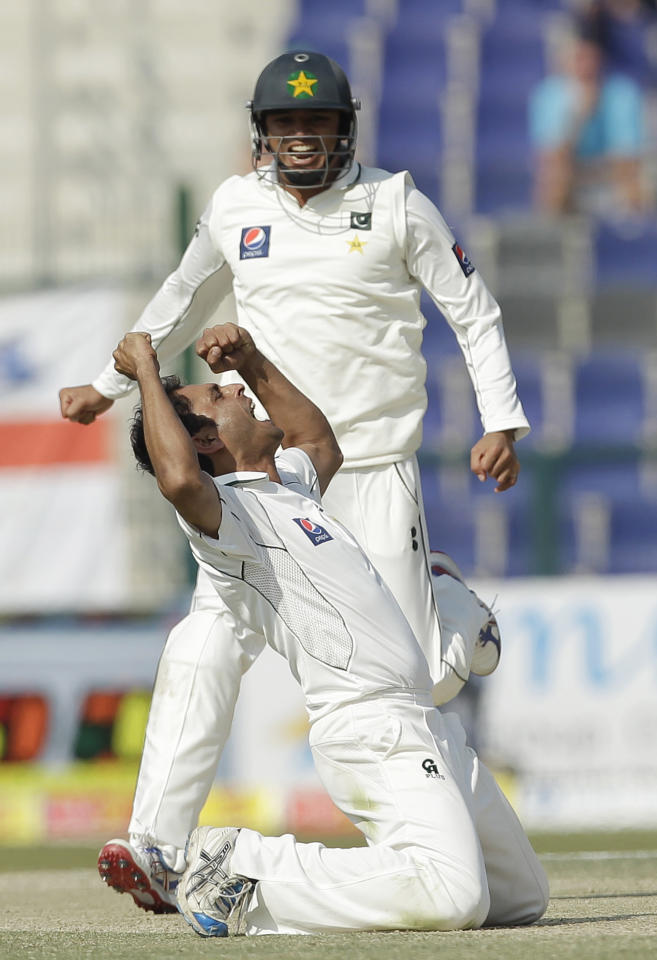 Pakistan's Abdur Rehman, ground, celebrates taking the wicket of England's Kevin Pietersen, not pictured, lbw as his teammate Azhar Ali runs during the fourth day of the second cricket Test match of a three match series between England and Pakistan at Zayed Cricket Stadium in Abu Dhabi, United Arab Emirates, Saturday, Jan. 28, 2012. (AP Photo/Hassan Ammar)