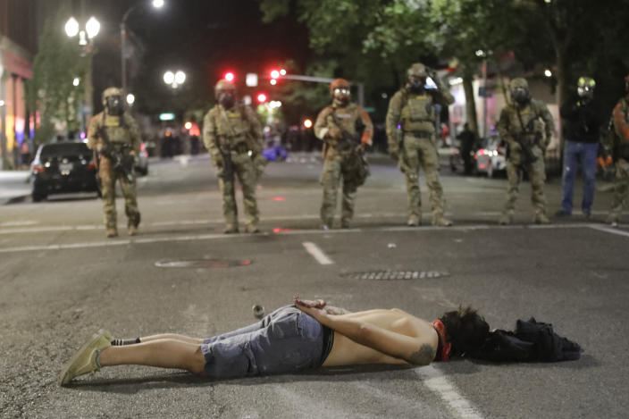 A demonstrator lays down in front of federal officers during a Black Lives Matter protest at the Mark O. Hatfield United States Courthouse Sunday, July 26, 2020, in Portland, Ore. (AP Photo/Marcio Jose Sanchez)