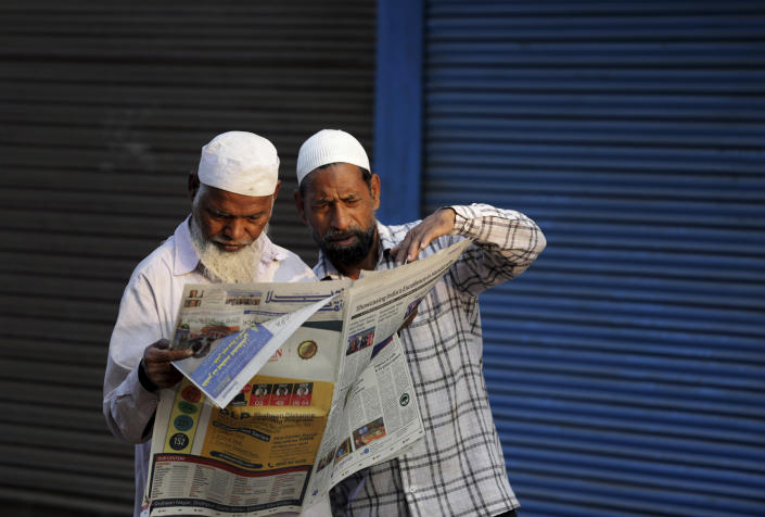 FILE - In this Nov. 10, 2019, file photo, Indian Muslims read a newspaper reporting about a Supreme Court verdict favoring the building of a Hindu temple on a site in a decades-old land title dispute between Muslims and Hindus in Ayodhya, India. As Hindus prepare to celebrate the groundbreaking of a long-awaited temple at a disputed ground in northern India, Muslims say they have no firm plans yet to build a new mosque at an alternative site they were granted to replace the one torn down by Hindu hard-liners decades ago. (AP Photo/Rajesh Kumar Singh, File)