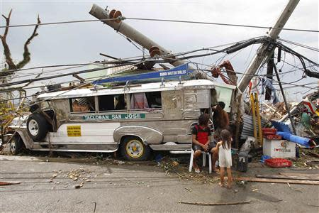 Survivors who lost their homes use a Jeepney public bus as shelter after a super Typhoon Haiyan battered Tacloban city, central Philippines November 9, 2013. REUTERS/Romeo Ranoco