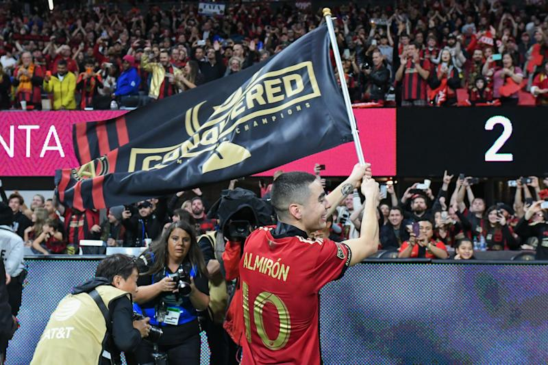 ATLANTA, GA DECEMBER 08: Atlanta's Miguel Almiron (10) waves a flag at the fans in the post-game celebration during the MLS Cup between the Portland Timbers and Atlanta United FC on December 8th, 2018 at Mercedes-Benz Stadium in Atlanta, GA. (Photo by Rich von Biberstein/Icon Sportswire via Getty Images)