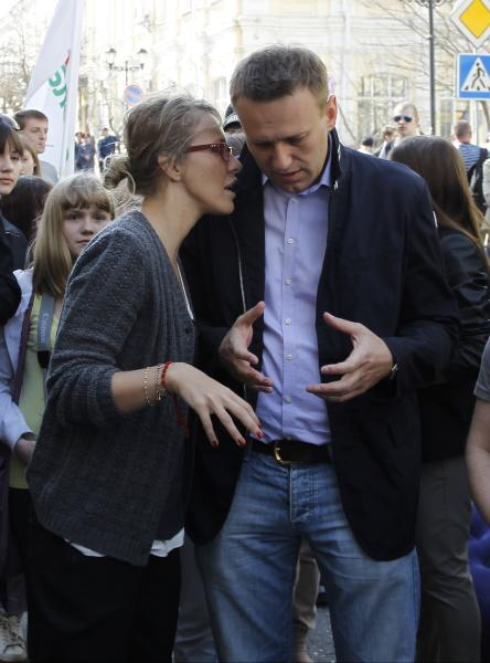 FILE - In this Saturday, April 14, 2012 file photo Russian opposition activist Kseniya Sobchak, left, speaks to anti-corruption campaigner and opposition leader Alexei Navalny while standing with other protesters during a rally in the southern Russian city of Astrakhan. Navalny finished first and Sobchak fourth in an online opposition election which was intended to help present a more united front against the Kremlin and find a way to broaden its appeal as enthusiasm for streets protests fades. (AP Photo/Yevgeny Polonsky, File)