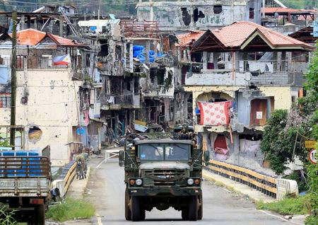 Soldiers on a military truck drive past houses and buildings damaged after government troops cleared the area from pro-Islamic State militant groups inside the war-torn Marawi city