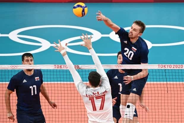 Poland's Mateusz Bieniek, right, hits the ball past Canadian Graham Vigrass, centre left, in the men's preliminary round pool A volleyball match that resulted in Poland winning 3-0 (25-15, 25-21, 25-16) over Canada on Sunday in Tokyo. (Anne-Christine Poujoulat/AFP via Getty Images - image credit)