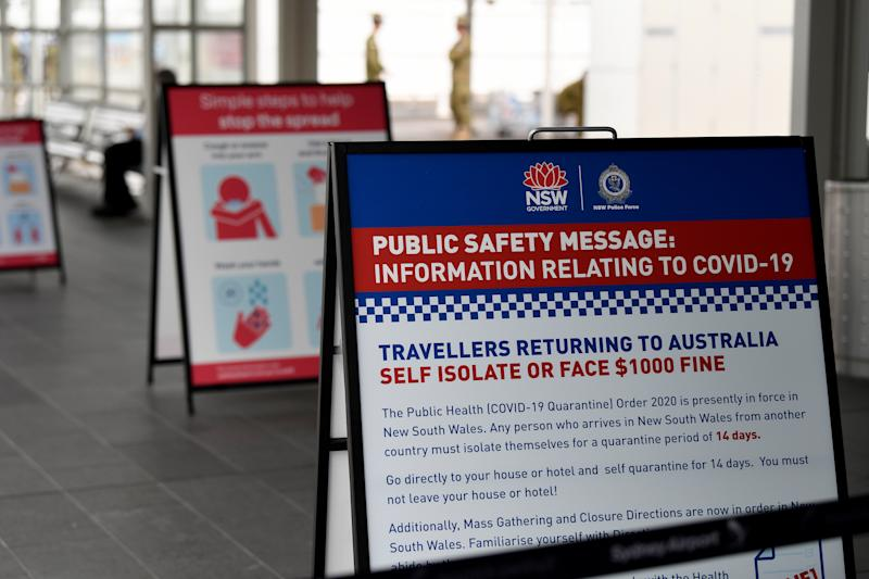 Picture of government signage is seen at the arrivals area at Sydney International Airport in Sydney, Monday, March 30, 2020.