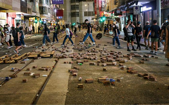 Passersby walk past bricks that have been dug up and laid out on the street as a way to slow down incoming police during demonstrations in Hong Kong - Katherine Cheng/SOPA Images/Shutterstock/ Shutterstock