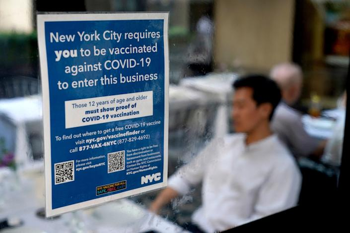 A sign explaining that proof of COVID-19 vaccination is required is seen at a restaurant in midtown Manhattan on Monday.