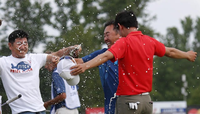 South Korean golfers Y.E. Yang, left, and Charlie Wi, center, douse Noh Seung-yul, right, with beer on the 18th green after Noh won the Zurich Classic golf tournament at TPC Louisiana in Avondale, La., Sunday, April 27, 2014.(AP Photo/Bill Haber)