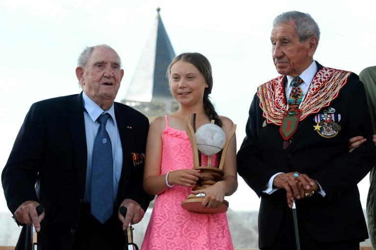 Swedish climate activist Greta Thunberg, flanked by WWII veteran and native American Charles Norman Shay (R), sponsor of the Freedom Award, and French WWII veteran Leon Gautier, poses with the Normandy 'Freedom prize' during the award ceremony (AFP Photo/JEAN-FRANCOIS MONIER                )