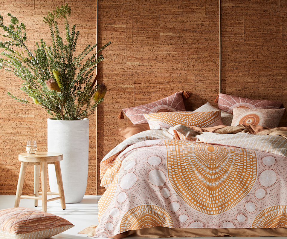 Image of a bed dressed with an indigenous orange and pink pattern quilt cover in front of a brown wall with a native plant to the right.