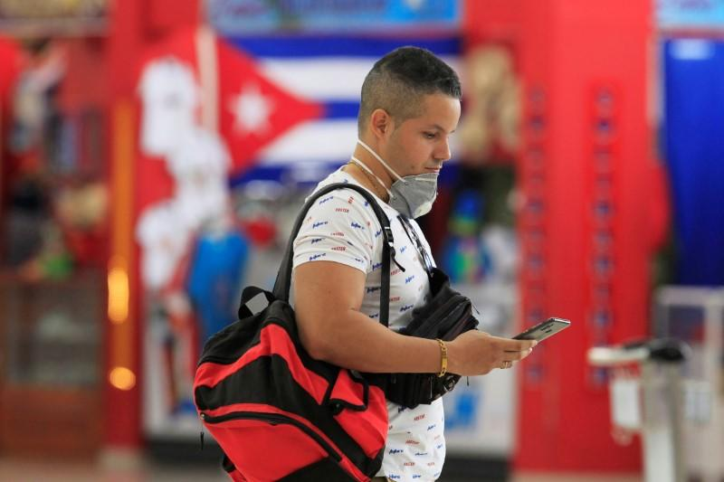A man with his face mask pulled down is seen at Jose Marti International Airport, in Havana