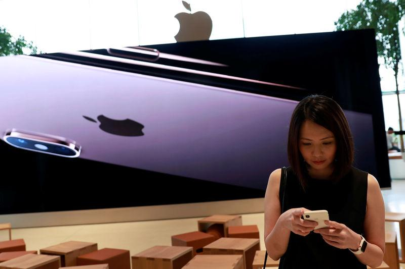 FILE PHOTO: A woman checks her phone at a flagship Apple store at Iconsiam shopping mall in Bankok