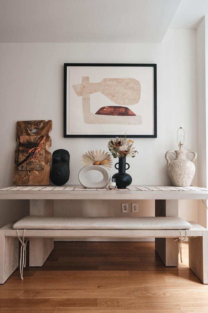 Above a table and bench set from Crate & Barrel, Candace displays a photograph by Samuel Trotter of the See in Black Collective, a Black female torso gifted by friend Zerina Akers (founder of Black Owned Everything), wall art from Crate & Barrel, and a vintage table lamp.