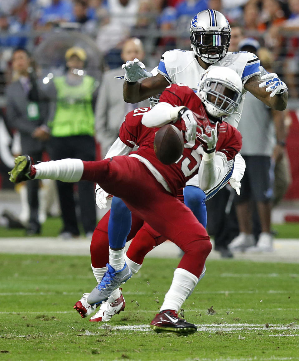 Arizona Cardinals cornerback Jerraud Powers, front, breaks up a pass intended for Detroit Lions wide receiver Calvin Johnson, rear, during the first half of an NFL football game, Sunday, Nov. 16, 2014, in Glendale, Ariz. (AP Photo/Ross D. Franklin)