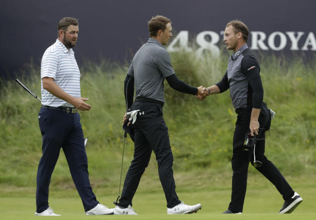 Jordan Spieth of the United States, centre, shakes hands with England's Danny Willett, right and Australia's Marc Leishman as they complete their second round of the British Open Golf Championships at Royal Portrush in Northern Ireland, Friday, July 19, 2019.(AP Photo/Matt Dunham)