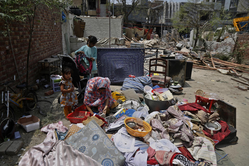 A family collects salvages belongings from their damaged houses at the site of a car bombing Wednesday, in Lahore, Pakistan, Thursday, June 24, 2021. Pakistani security forces on Thursday arrested one of the alleged perpetrators of the car bombing that killed at least three people and wounded some 25 others near the residence of a jailed anti-India militant leader Hafiz Saeed, in the eastern city of Lahore, officials said. (AP Photo/K.M. Chaudary)