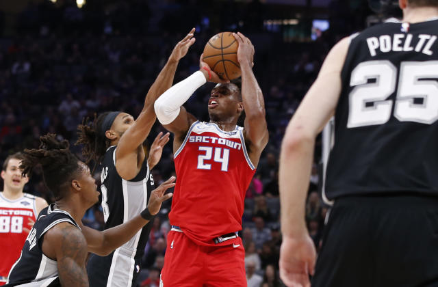 San Antonio Spurs guard Patty Mills, second from left, tries to block the shot of Sacramento Kings guard Buddy Hield during the first quarter of an NBA basketball game in Sacramento, Calif., Saturday, Feb. 8, 2020. (AP Photo/Rich Pedroncelli)
