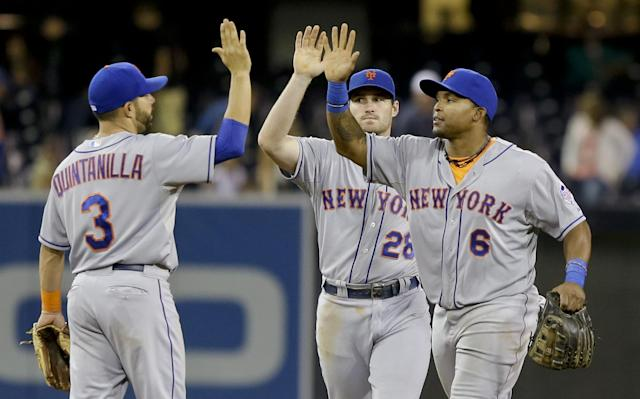 New York Mets' Marlon Byrd, right, and Daniel Murphy high five with Omar Quintanilla after the Mets 4-1 victory over the San Diego Padres in a baseball game Thursday, Aug. 15, 2013, in San Diego. Byrd collected two hits and broke up a tied game with a two run double in the eighth inning. (AP Photo/Lenny Ignelzi)