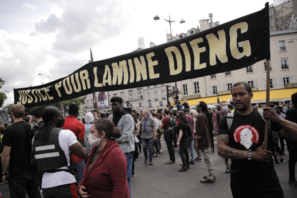 People march holding a banner during a protest in memory of Lamine Dieng, a 25-year-old Franco-Senegalese who died in a police van after being arrested in 2007, in Paris, Saturday, June 20, 2020. Multiple protests are taking place in France on Saturday against police brutality and racial injustice, amid weeks of global anger unleashed by George Floyd's death in the US. (AP Photo/Christophe Ena)