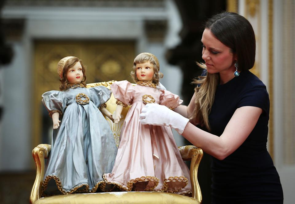 LONDON, ENGLAND - APRIL 02:  Royal Collection Trust Curator Anna Reynolds adjusts Parisian dolls belonging to Queen Elizabeth II (L) and Princess Margaret at Buckingham Palace ahead of the Royal Childhood exhibition on April 2, 2014 in London, England. Spanning more than 250 years the exhibition brings together objects from the Royal Collection, the Royal Archives and the private collections of members of the Royal Family, as well as previously unseen photographs and film footage. Royal Childhood is part the Summer Opening of the State Rooms at Buckingham Palace from July 26, 2014 to September 28, 2014.  (Photo by Peter Macdiarmid/Getty Images)
